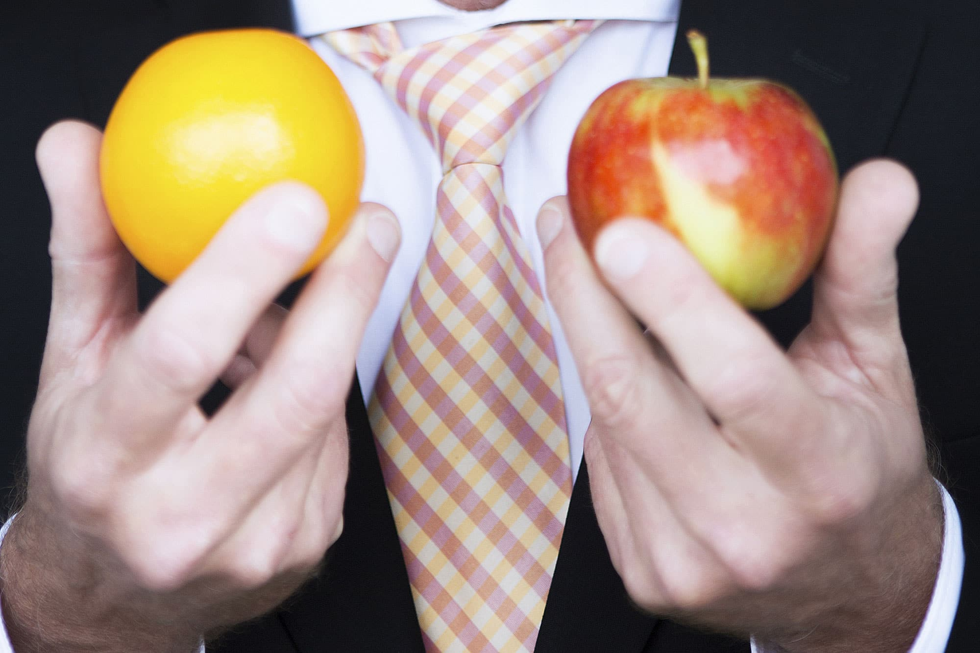 Man in a suit comparing apples and oranges