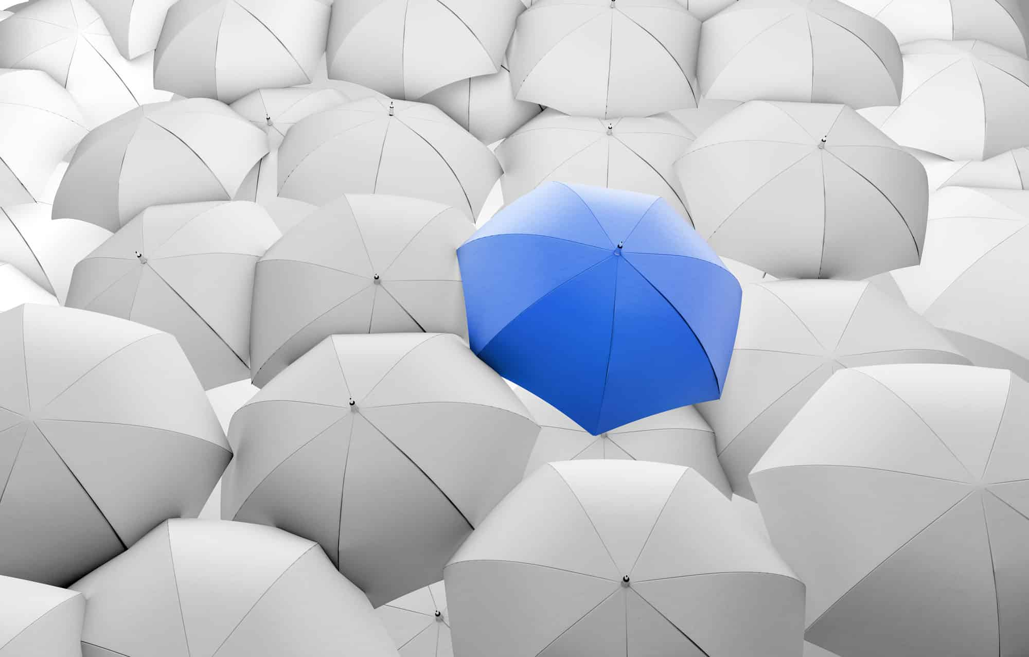 One blue umbrella surrounded by white umbrellas