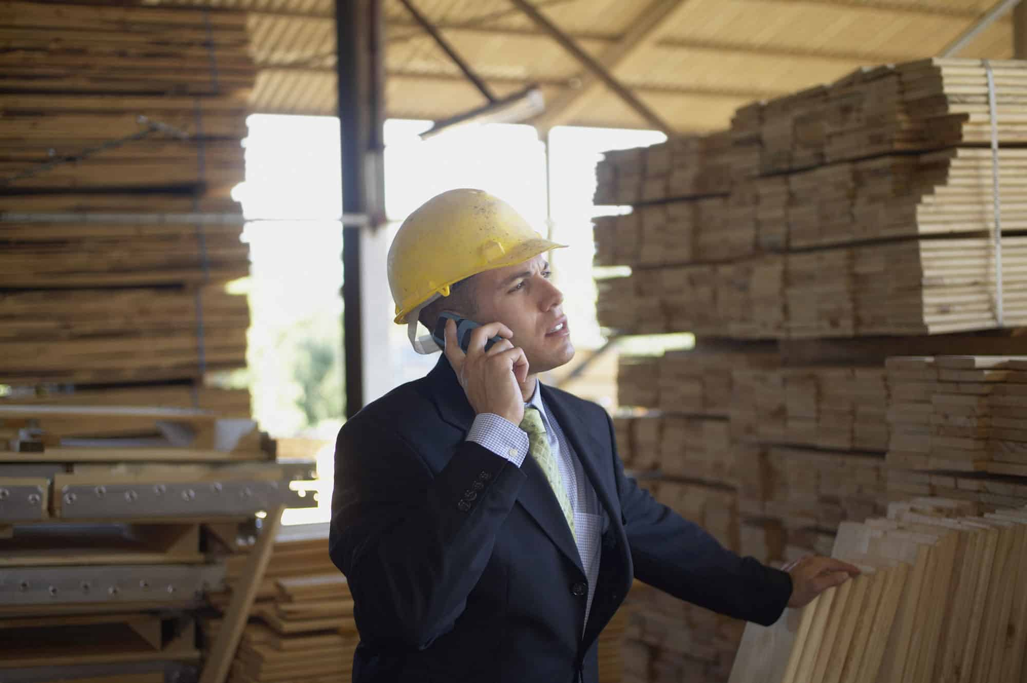 Man in a suit and hard hat talking on the phone in a lumber yard
