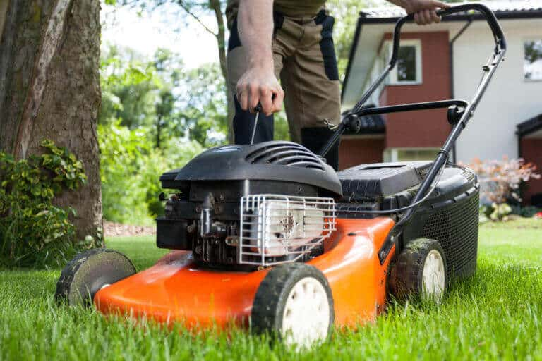 A property preservation contractor mows the lawn of a foreclosed home