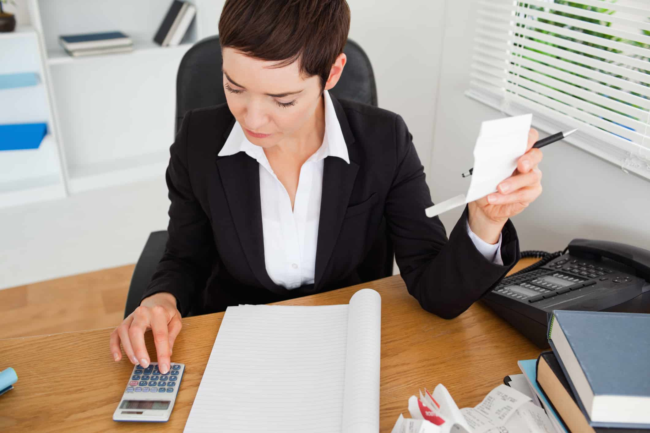White woman in a suit using a calculator to tally receipts