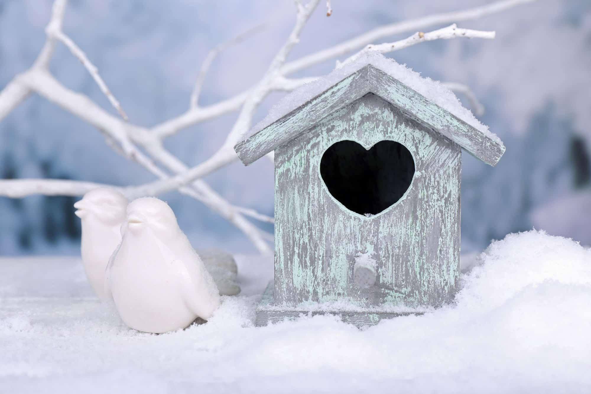 snowy scene of a bird house and ceramic birds