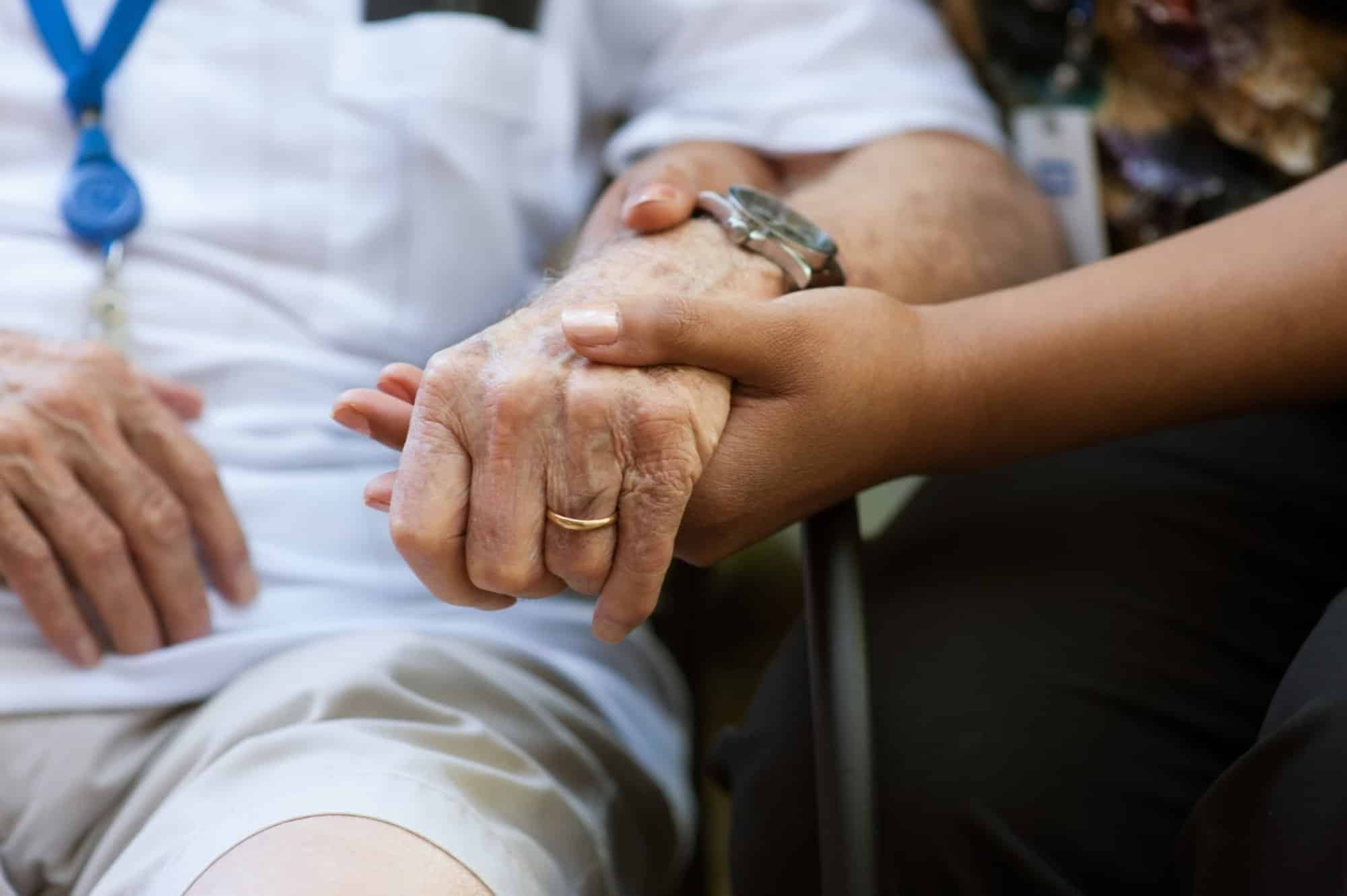 A young person holding the hand of an elderly person