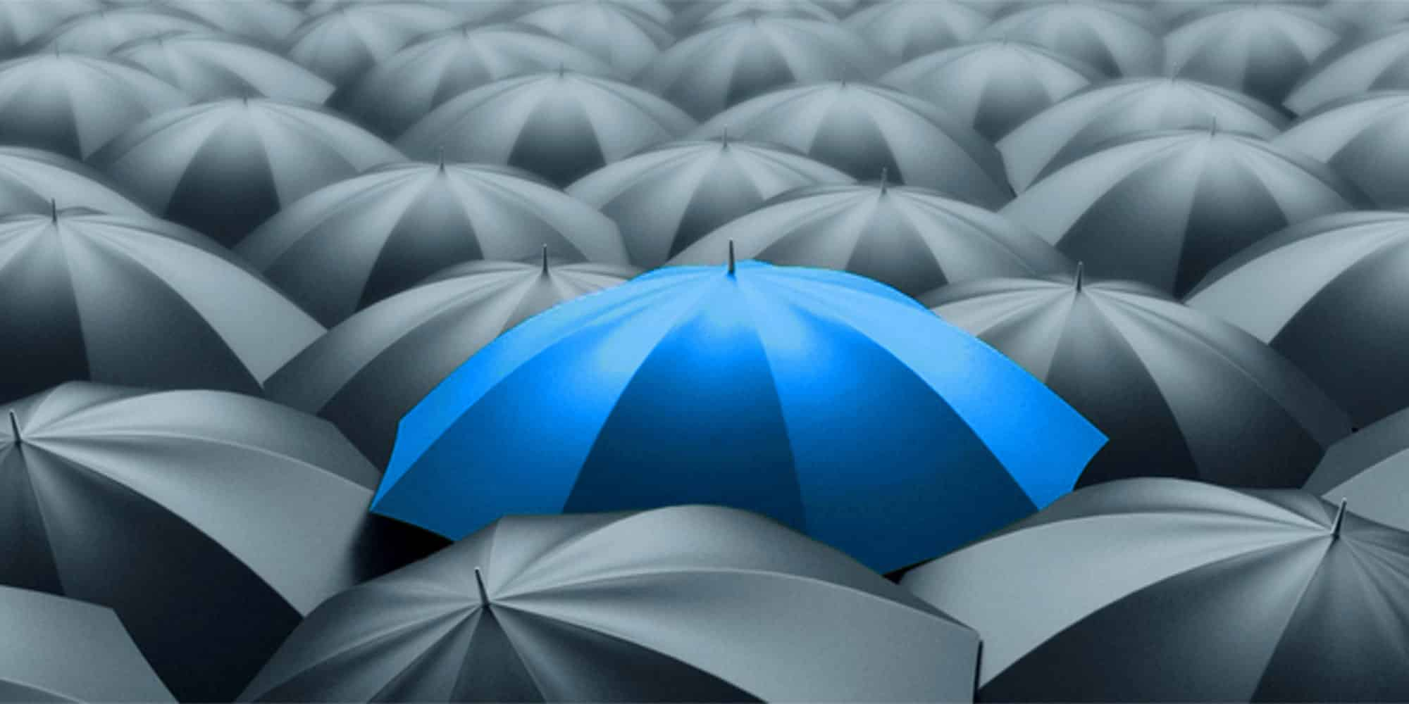 one blue umbrella surrounded by black umbrellas