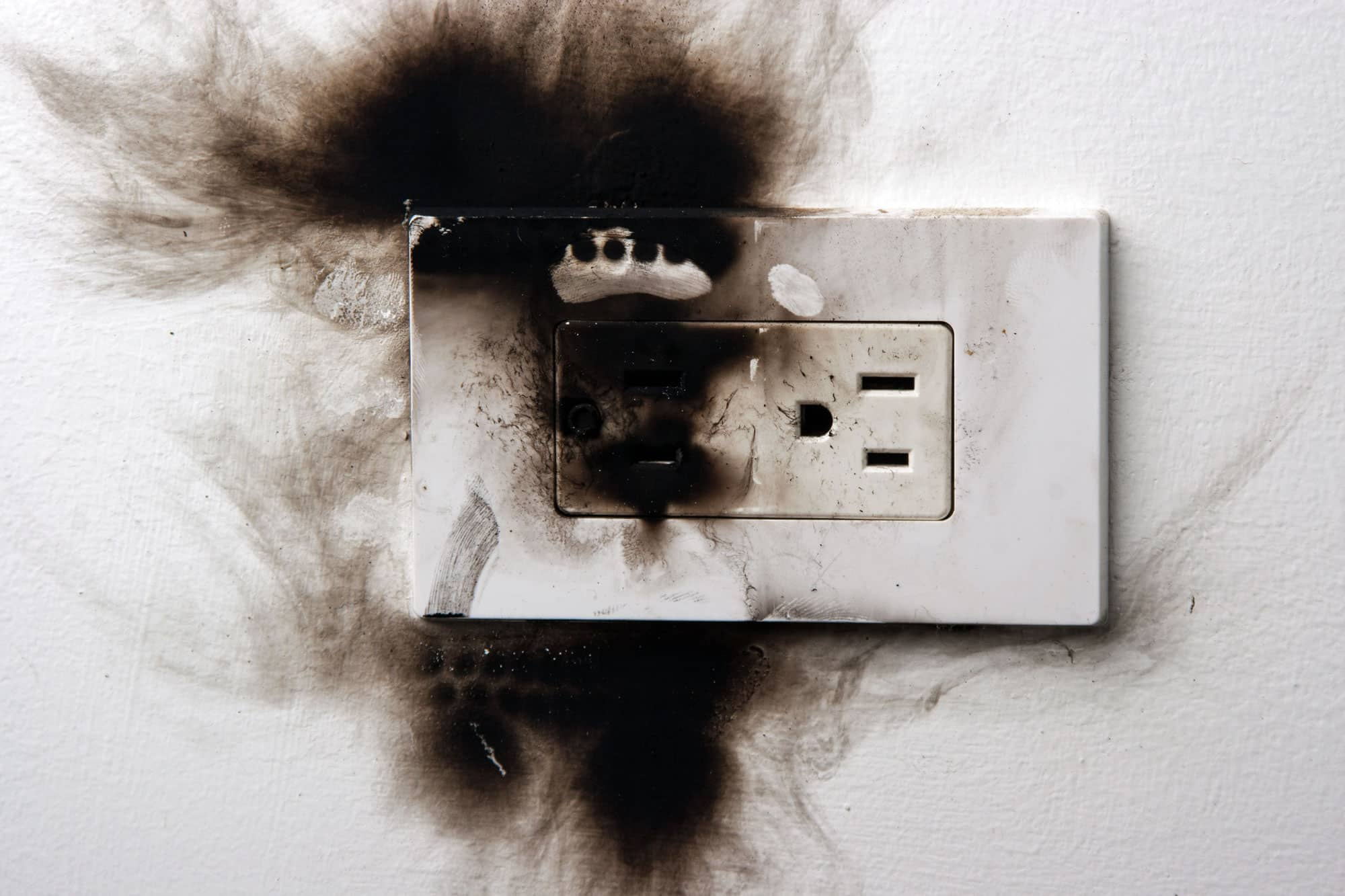 A wall outlet showing fire damage