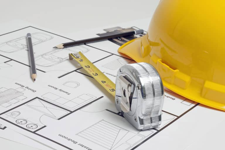 hard hat with tape measure sitting on a floor plan